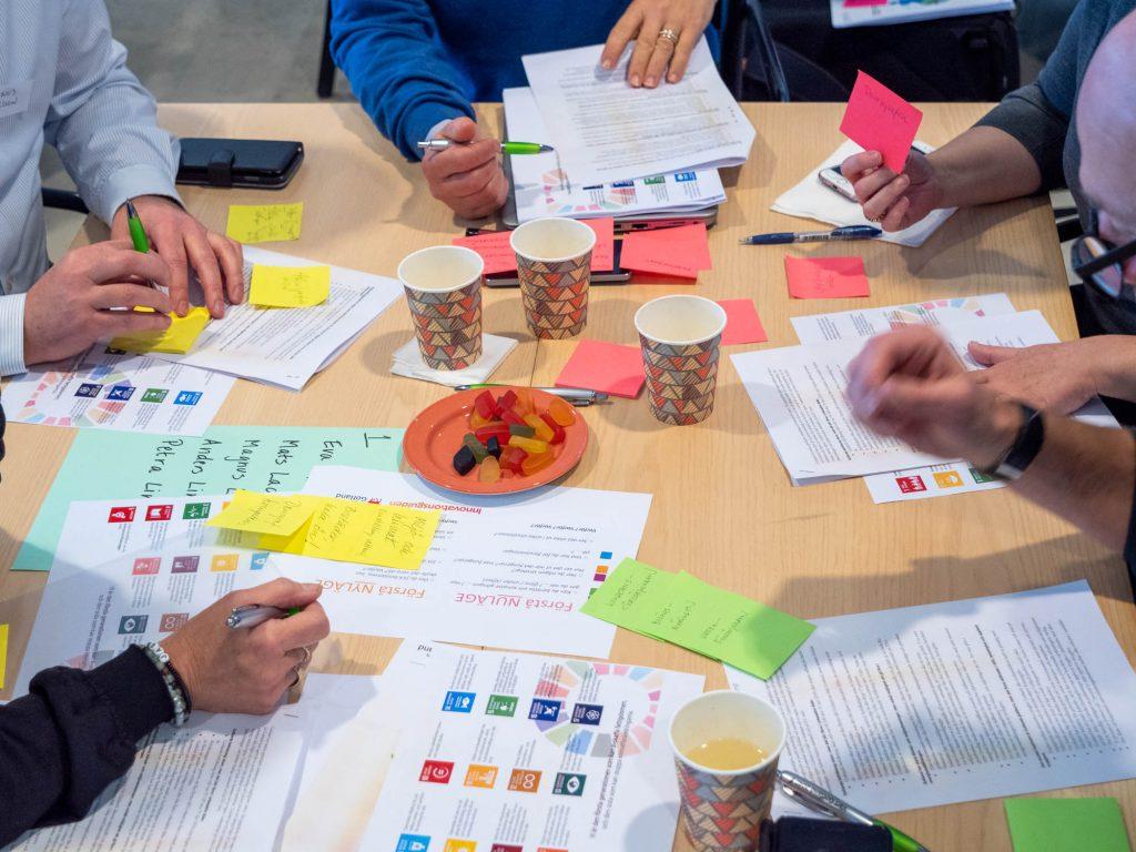 Personer runt ett bord med papper, post-its, kaffemuggar och godis.